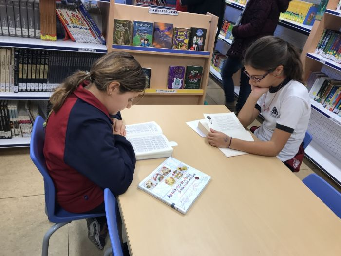 Niñas leyendo en la biblioteca escolar de Primaria